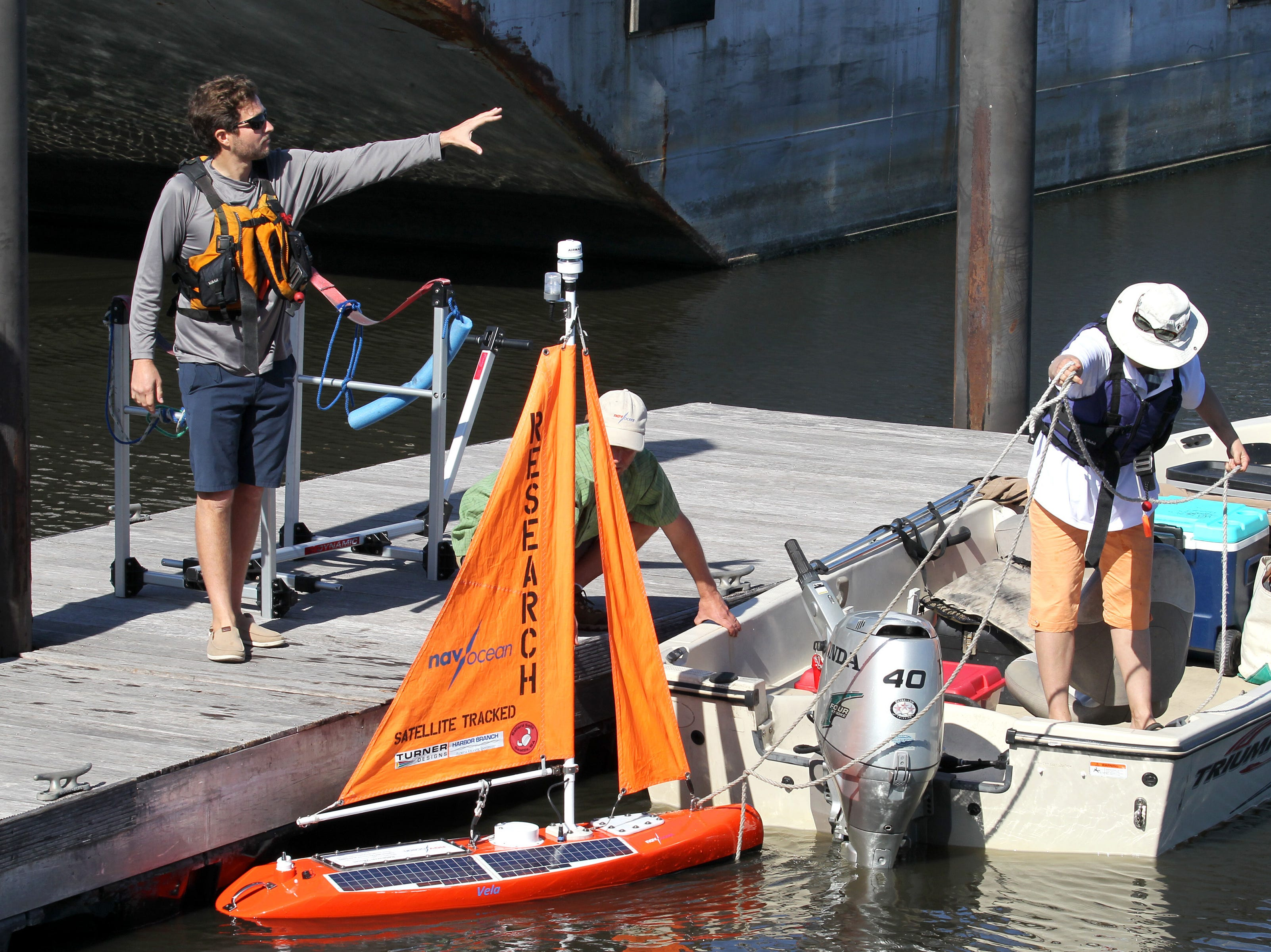 Jordon Beckler, assistant research professor at FAU Harbor Branch Oceanographic Institute (from left), Scott Duncan, president and chief designer at Navocean, and his assistant and field tech Pamela Cragin, prepare to tow Navocean's Nav2, the first autonomous sailboat for algae monitoring, from the dock of the Pahokee Marina into Lake Okeechobee on Tuesday, Feb. 5, 2019 in Pahokee.