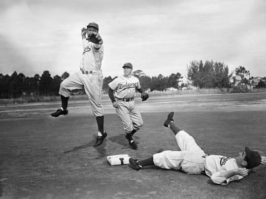 Jackie Robinson, Brooklyn Dodgers infielder, leaps into the air as he and Dodgers' captain Pee Wee Reese (center) practice double plays at the Dodgers Vero Beach, Florida, spring training camp March 4, 1949. Dodgers minor league prospect Orville Stammen slides into second base. (AP Photo)