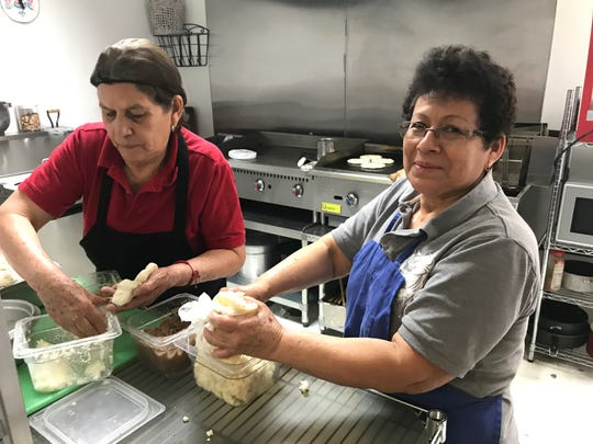 Sisters Miriam Pacheco, left, and Isabel Pacheco are the queens of the pupusas in the restaurant kitchen. The recipe is Isabel's.