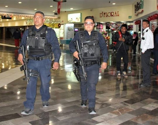 Juárez police officers patrol a shopping mall during the holiday season in 2018.