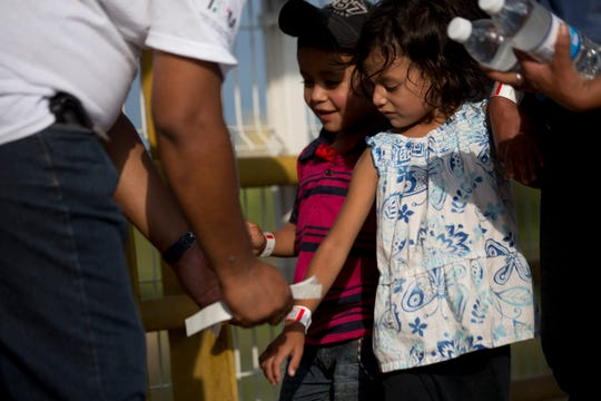 Honduran children receive a processing bracelet from a Mexican migration worker as they enter Mexico from Guatemala, near Ciudad Hidalgo, Chiapas State, Mexico, on Thursday, Jan. 17, 2019. Hundreds of mainly Honduran migrants began crossing peacefully into Mexico without the confrontations that marked last fall's migrant caravans.