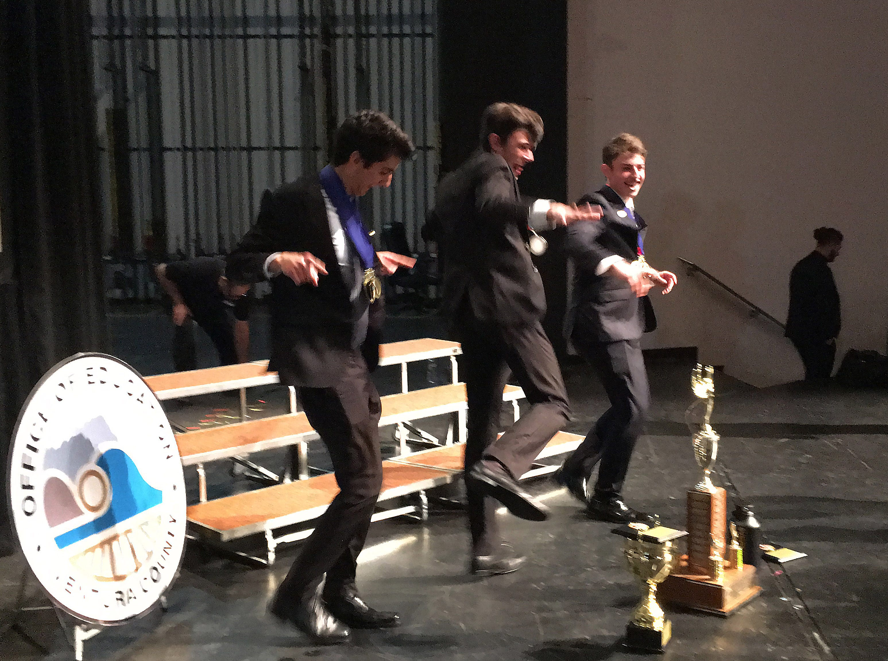 From left, Daniel Shishegar, Bennett Cohen and Maxon Repass, of Calabasas High School, celebrate on stage after their school was named winner of the Ventura County Academic Decathlon for a third year in a row at the awards ceremony on Monday.