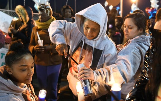 Kenthy Street (center), mother of Walter L. Brown, and Carmen Rosario (right), Brown's longtime companion, light candles during a vigil at the Vineland Midget Football grounds on Monday, Feb. 4, 2019. Brown was fatally shot during a reported home invasion last week.
