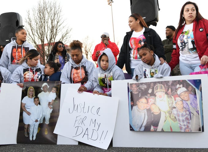 """Walter L. Brown's family gather for a vigil at the Vineland Midget Football grounds on Monday, Feb. 4, 2019. Brown's mother, Kenthy Street, and his son, Walter (center) hold a sign reading """"Justice For My Dad!!"""" while Jeff Lindsey speaks to the crowd. Brown was fatally shot during a reported home invasion last week."""