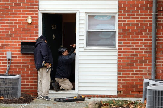 Maintenance workers repair the door for apartment 52A at Warren Hills apartment complex in Nyack Feb. 5, 2019. Feds raided the apartment in a drug sweep earlier in the morning.