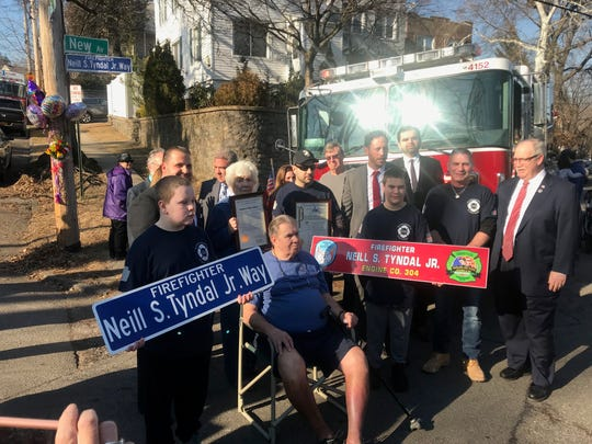 Neill Tyndal Jr.'s parents and sons, Matthew on the left and Neill on the right pose Feb. 5, 2019, after their block on New Avenue in Yonkers was renamed in Tyndal's memory on what would have been his 50th birthday. Tyndal died Sept. 19, 2017, of 9/11 related illness.