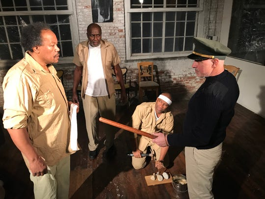 "Left to right: Keith Bulluck (as Nelson Mandela), Kevin Barksdake, Steve Allen (kneeling) and John DeBlasio from the production of ""Antigone on Robben Island: Nelson Mandela Takes the Stage."""
