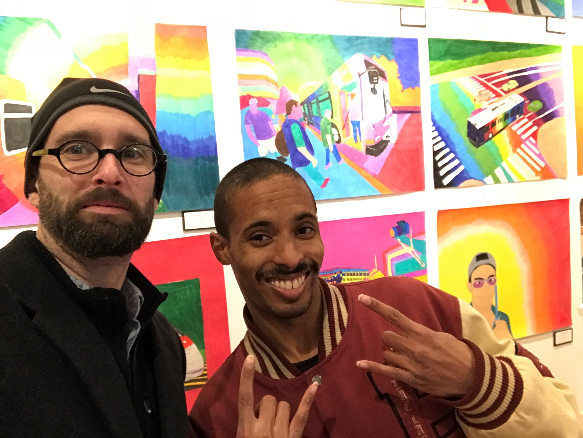 Michael Kalmbach, left, executive director of the Creative Vision Center, and transportation artist Geraldo Gonzalez celebrate the opening of his show on Market Street in Wilmington.
