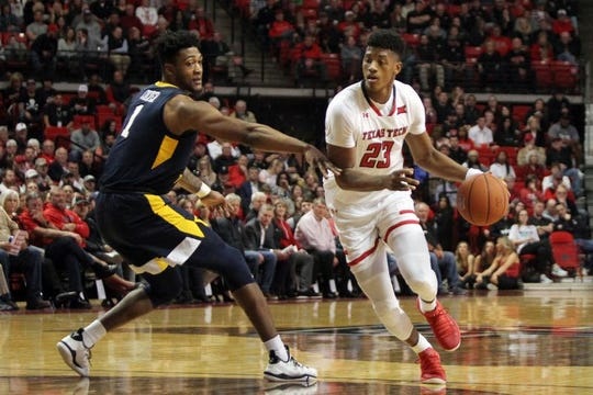 Texas Tech guard Jarrett Culver (23) drives the ball around West Virginia  forward Derek Culver (1) on Monday.