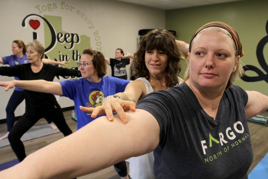 Vicki Schweiss corrects Beth Combs form in Schweiss's yoga studio Deep in the Heart.