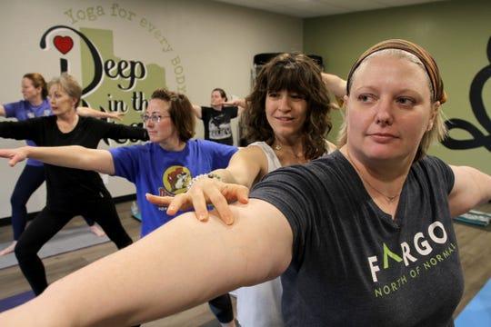 Vicki Schweiss corrects Beth Combs form in Schweiss's yoga studio Deep in the Heart.
