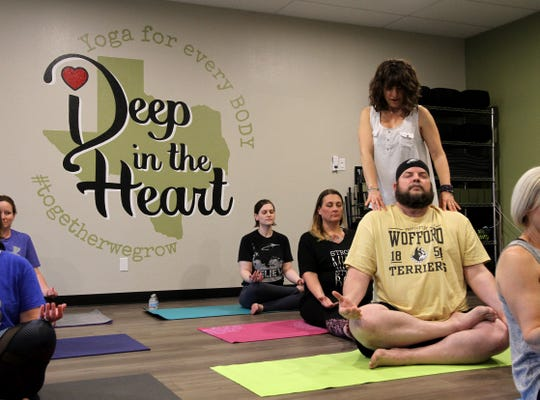 Vicki Schweiss corrects the form of one of her students in her yoga studio Deep in the Heart.