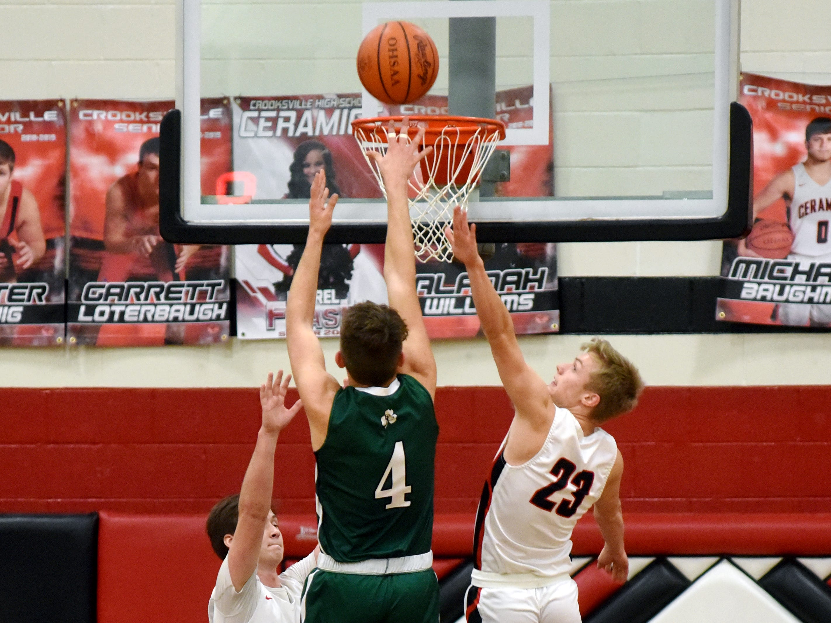 Fisher Catholic's Daniel Turner shoots a jumper over Crooksville's Caden Sparks on Monday night in McLuney.