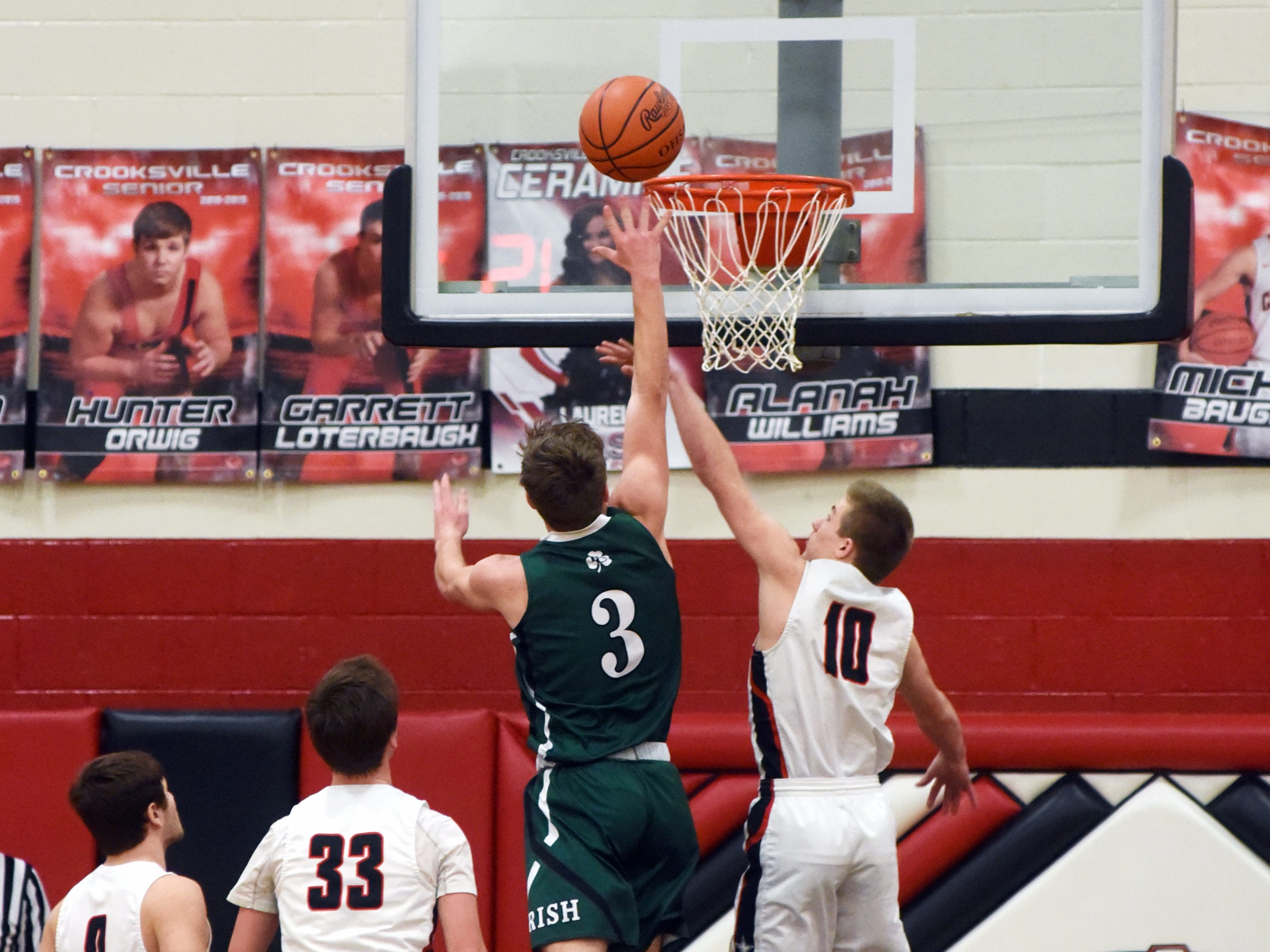Fisher Catholic's Collin McCrady shoots over Crooksville's Hunter Carr on Monday night in McLuney.