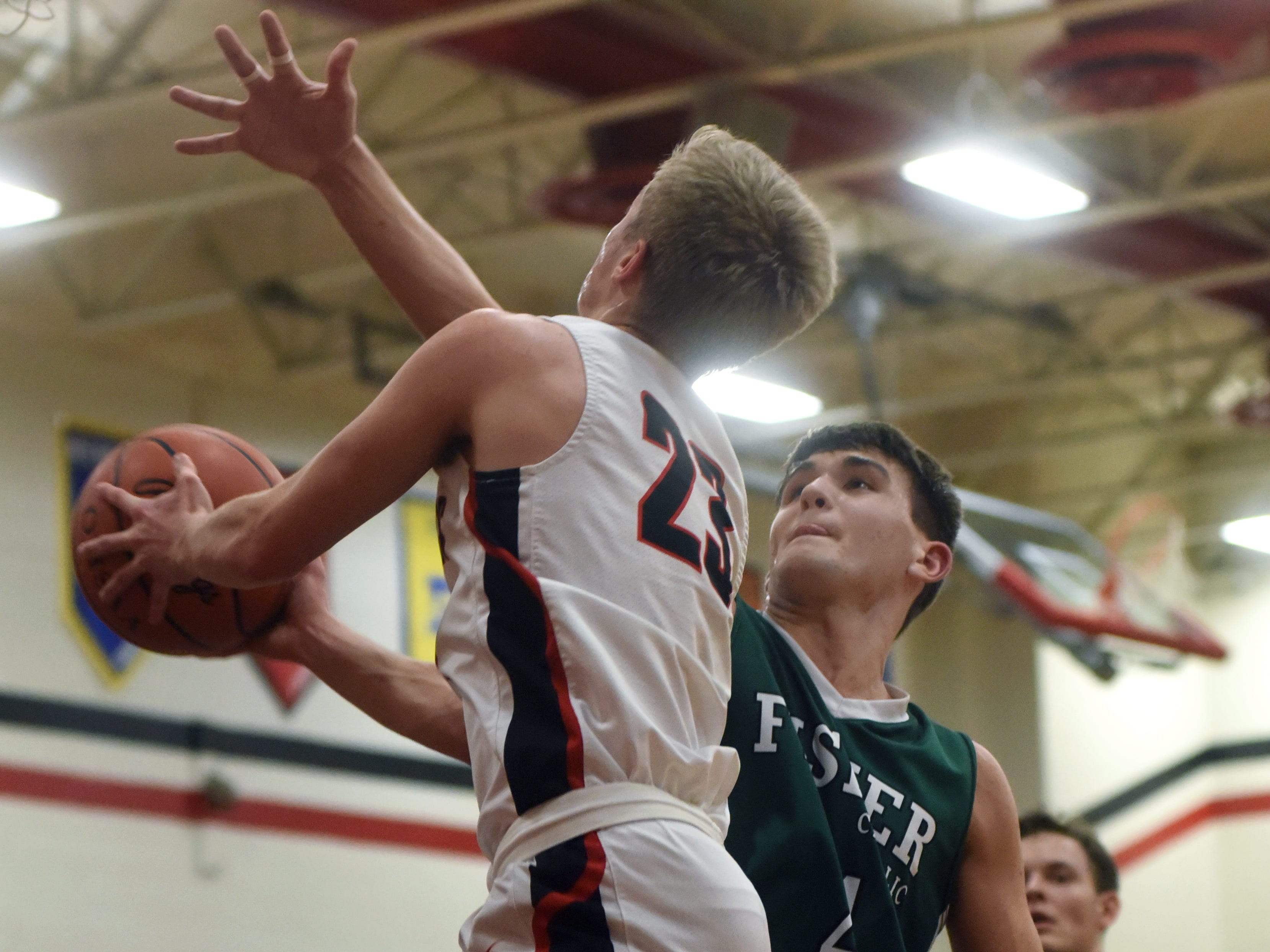 Daniel Turner, of Fisher Catholic, tries to block the shot of Crooksville's Caden Sparks on Monday night in McLuney.