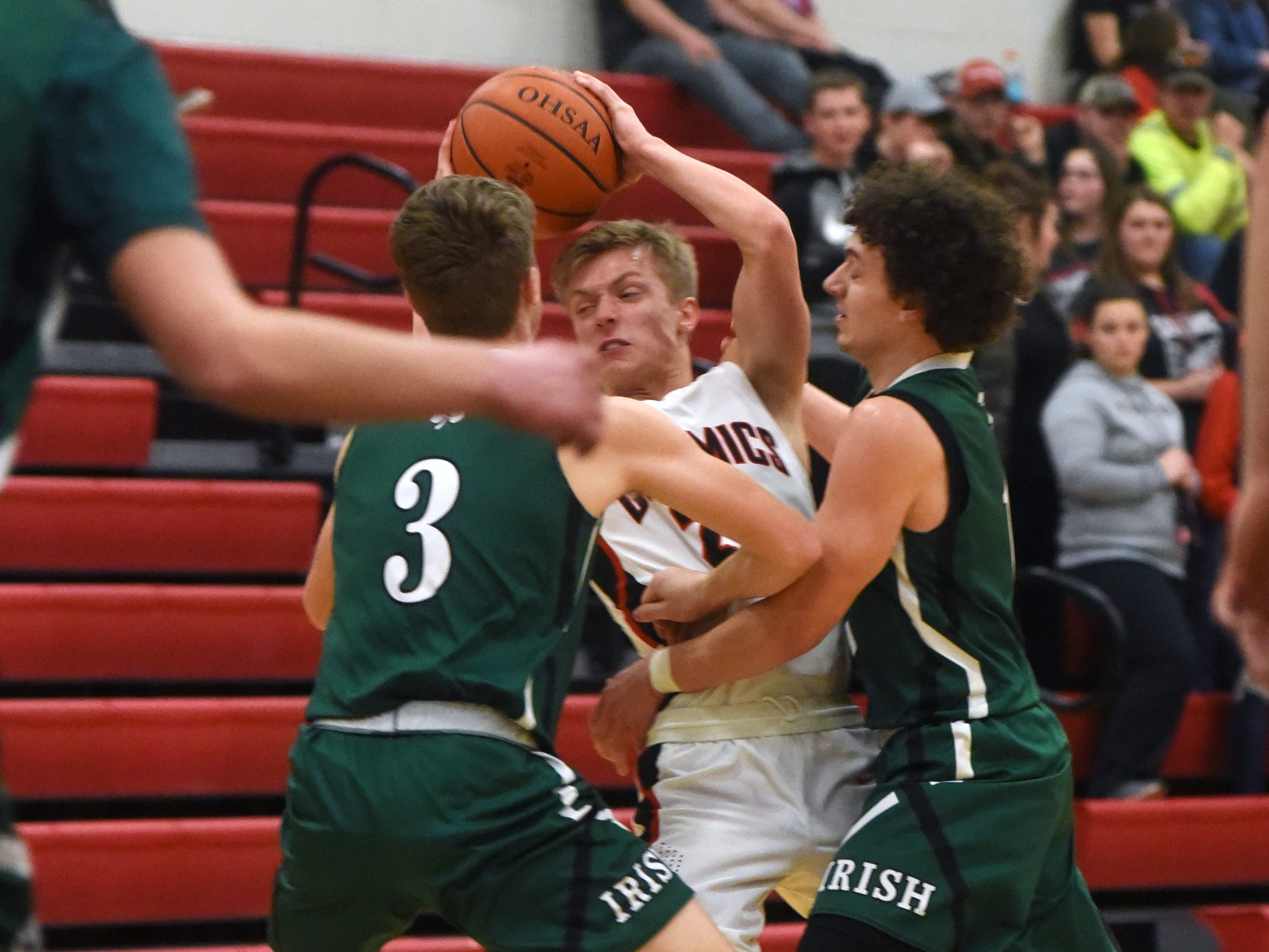 Crooksville's Caden Sparks is trapped by Collin McCrady, left, and Payton Shockley, of Fisher Catholic, on Monday night in McLuney.