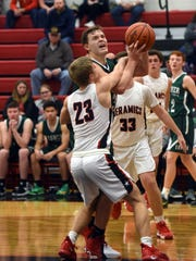Bailey Francis is fouled going up for a shot during Fisher Catholic's 66-56 win against Crooksville on Monday night in McLuney.