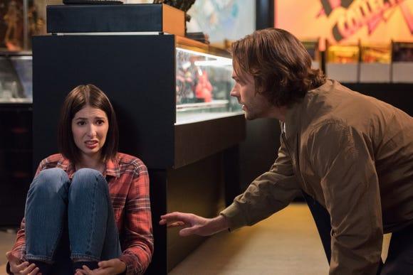 "Sam (Jared Padalecki) comforts a shaken store clerk (Genevieve Buechner) on ""Supernatural."""