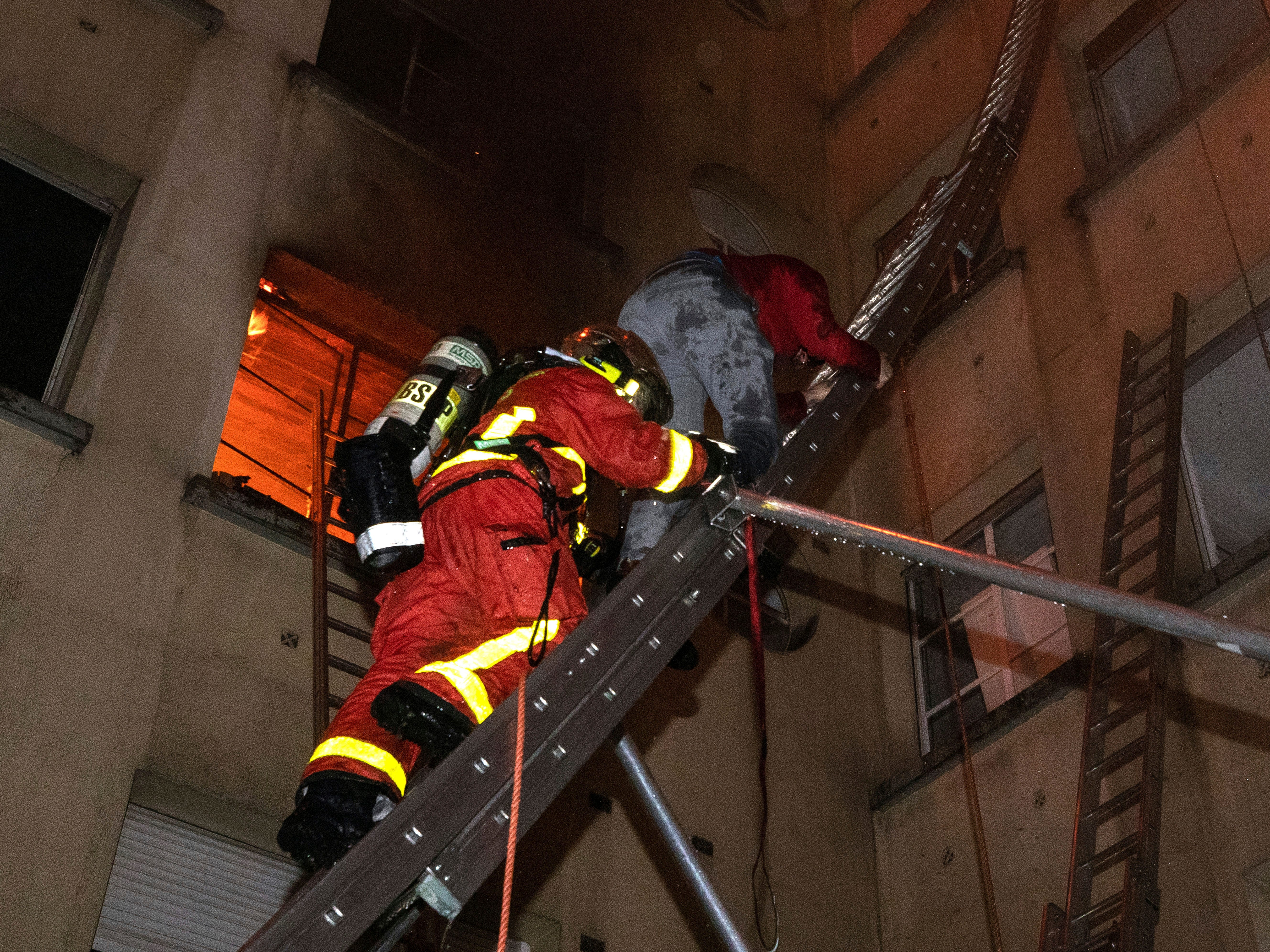 In this image provided on Feb. 5, 2019 by the Paris Fire Brigade a resident of an apartment building escapes a fire as he is evacuated by a firefighter, in Paris, France.