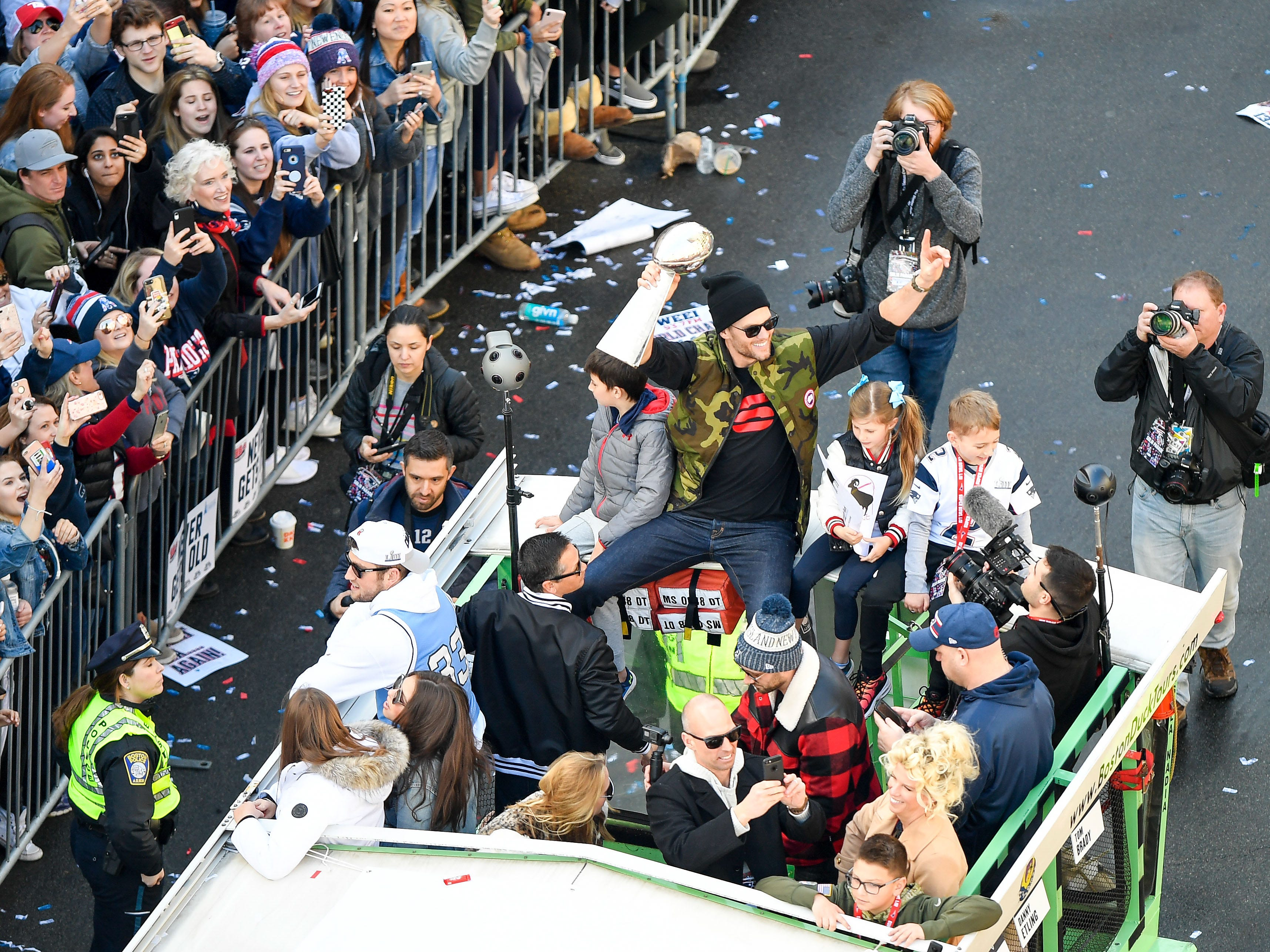 New England Patriots quarterback Tom Brady holds up the Lombardi Trophy as he rides a duck boat on Boylston Street during the Super Bowl LIII championship parade near Copley Square.