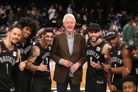 Former President Bill Clinton poses for a photo with the Brooklyn Nets hype crew after a game against the Milwaukee Bucks.