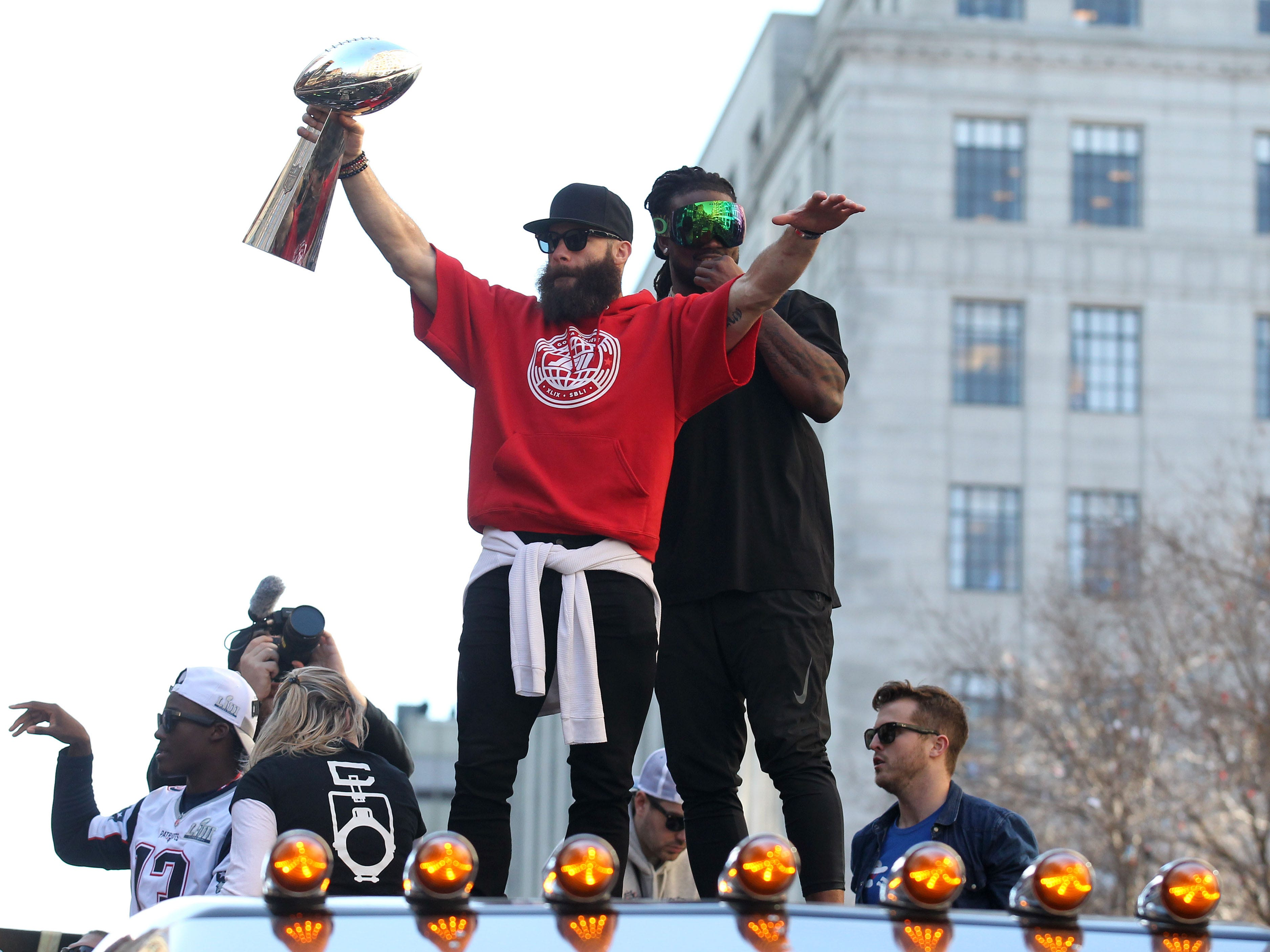 New England Patriots wide receiver Julian Edelman hoists the Lombardi Trophy as he rides a truck during the Super Bowl LIII championship parade.