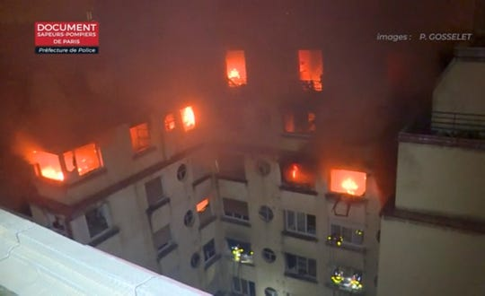 In this image taken from video released by the Paris Fire Department, a fire rages through the top floors of an apartment building early Tuesday in Paris.
