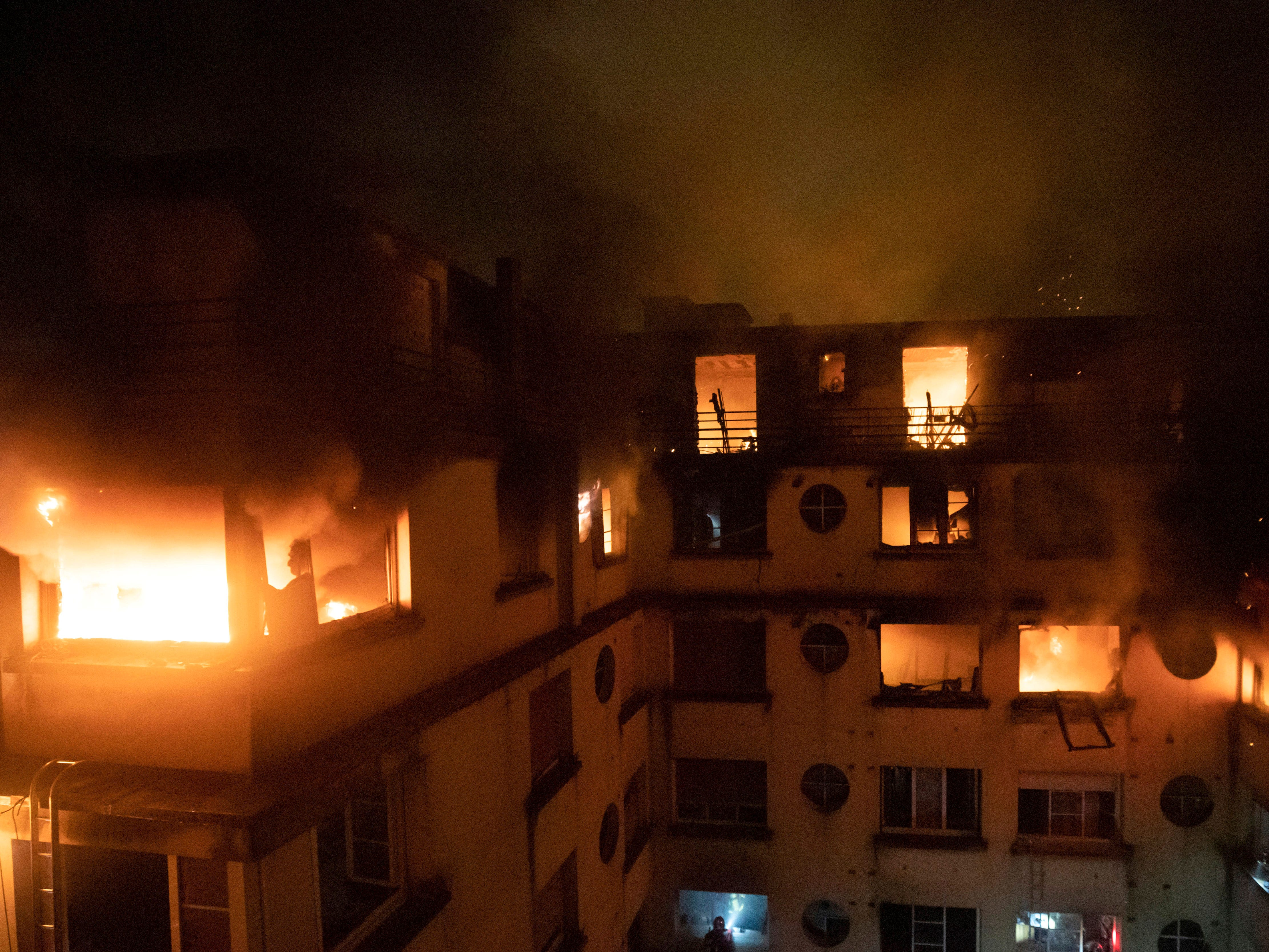 In this photo provided on Feb. 5, 2012 by the Brigade de Sapeurs-Pompiers de Paris (Paris Fire Brigade), a fire rages through the top floors of an apartment building in Paris, France. A woman has been arrested over a deadly blaze that killed ten people in Paris and police are treating the fire as a possible arson attack, a prosecutor said early on February 5.