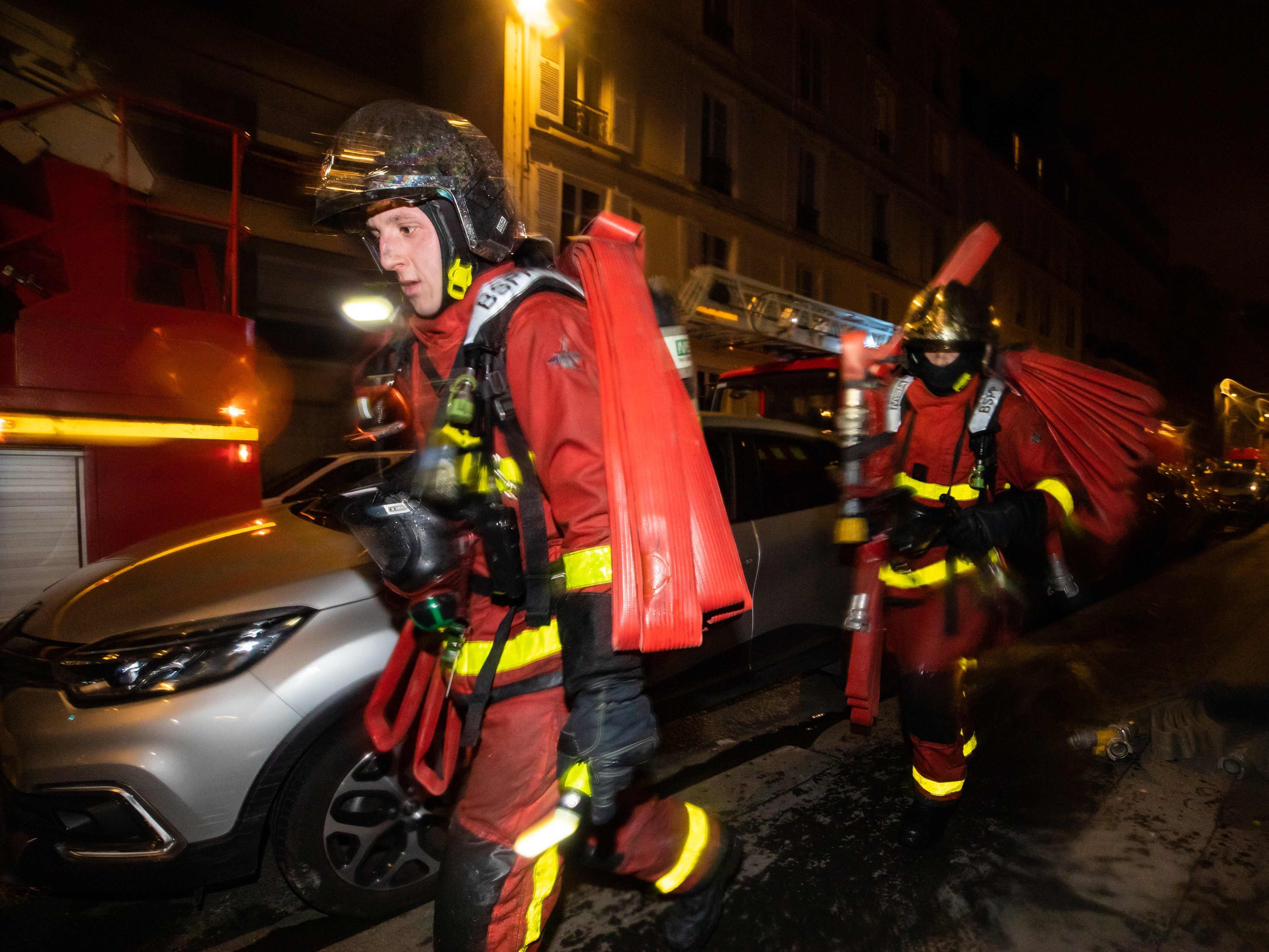 This handout picture taken and released by the Paris firefighters brigade shows firemen carrying gear as a fire burns in a building in Erlanger street in the 16th arrondissement in Paris.