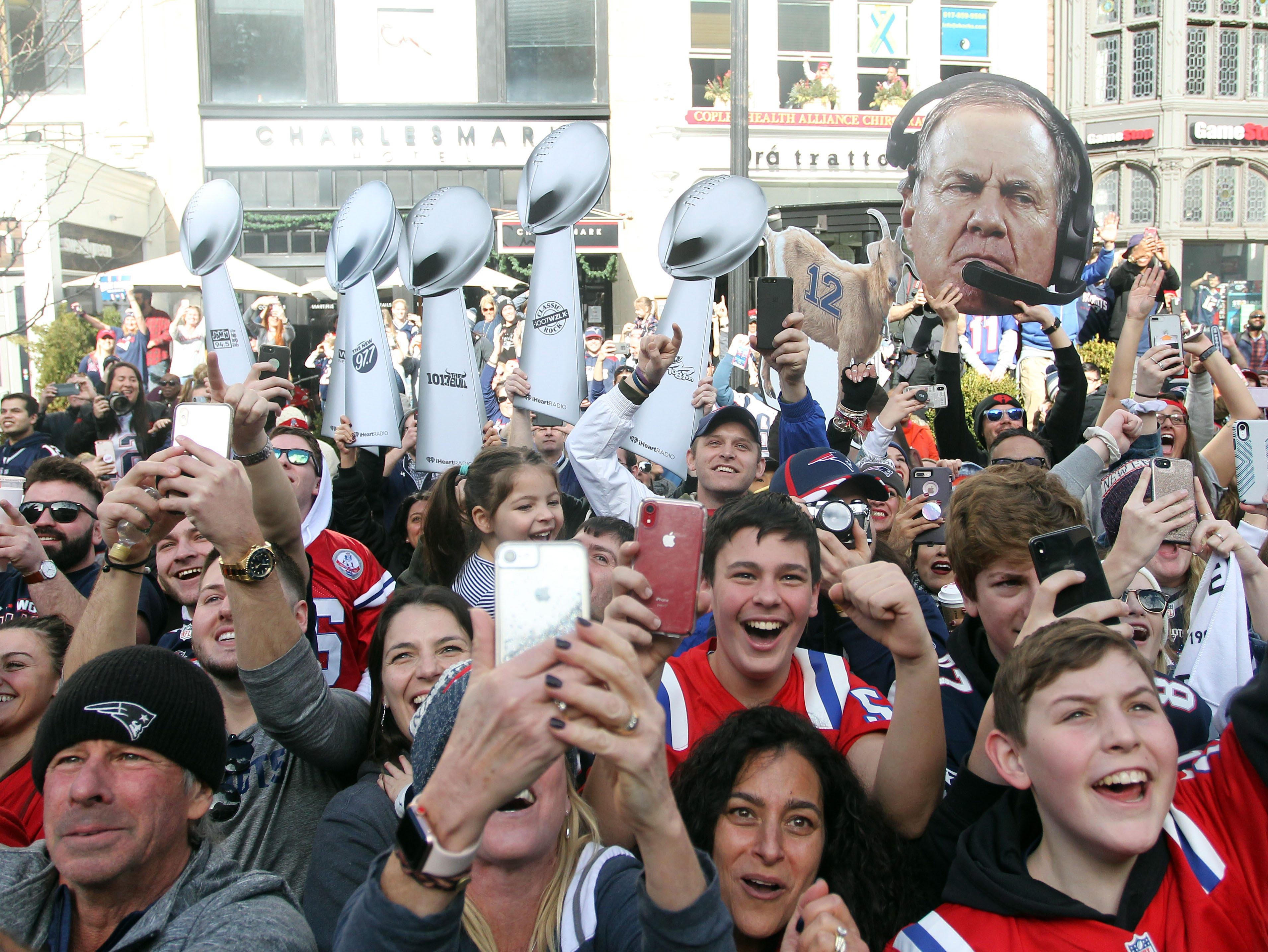 New England Patriots  fans cheer on as New England Patriots head coach Bill Belichick , not pictured, rides by in a duck boat during the Super Bowl LIII championship parade.