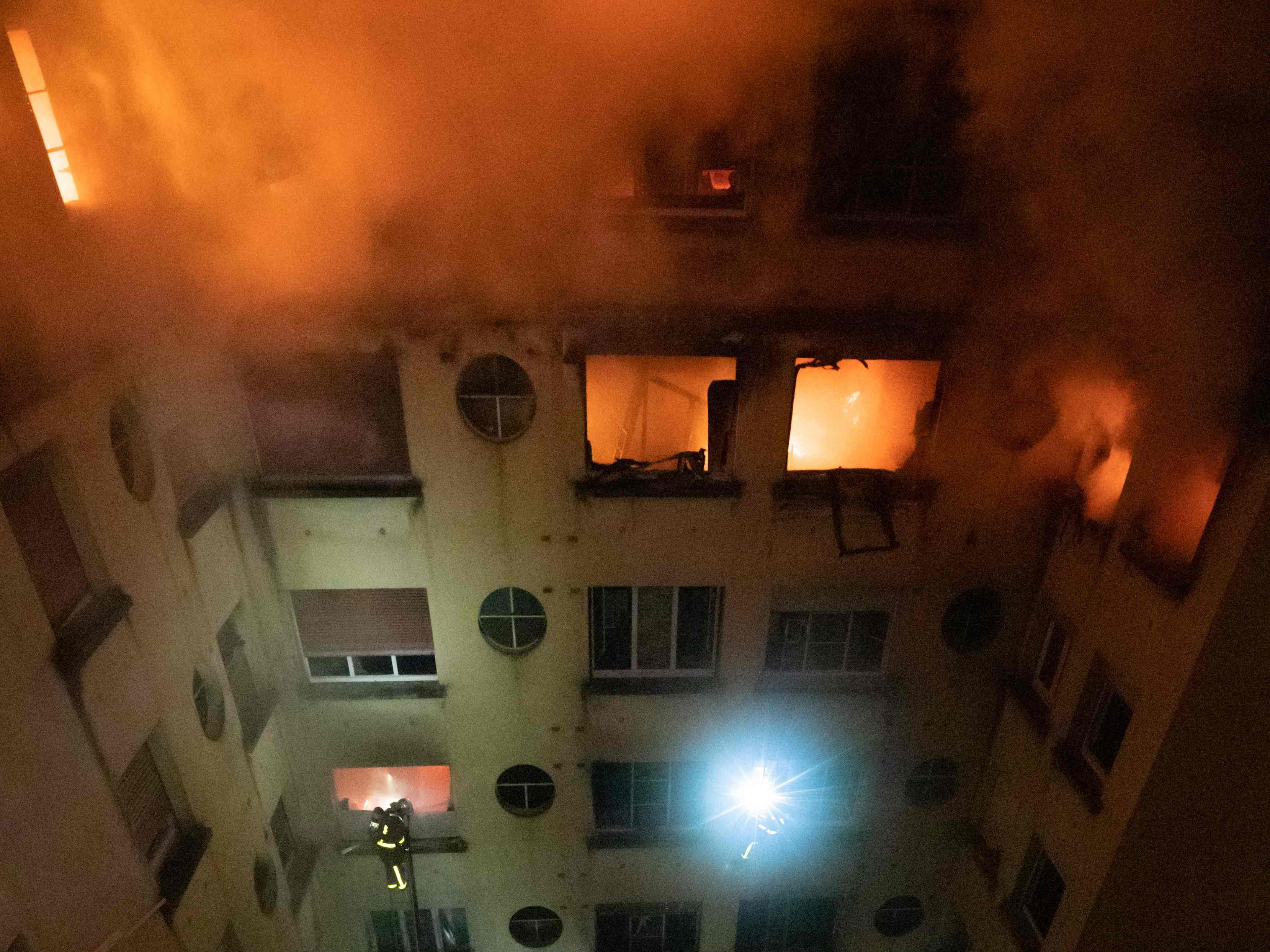 This handout picture taken and released by the Paris firefighters brigade in the night of February 5, 2019 shows firemen working as a fire burns in a building in Erlanger street in the 16th arrondissement in Paris.