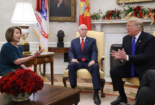 President Donald Trump is pictured speaking with House Minority Leader Nancy Pelosi (D-CA) as Vice President Mike Pence (center) sits nearby in the Oval Office.
