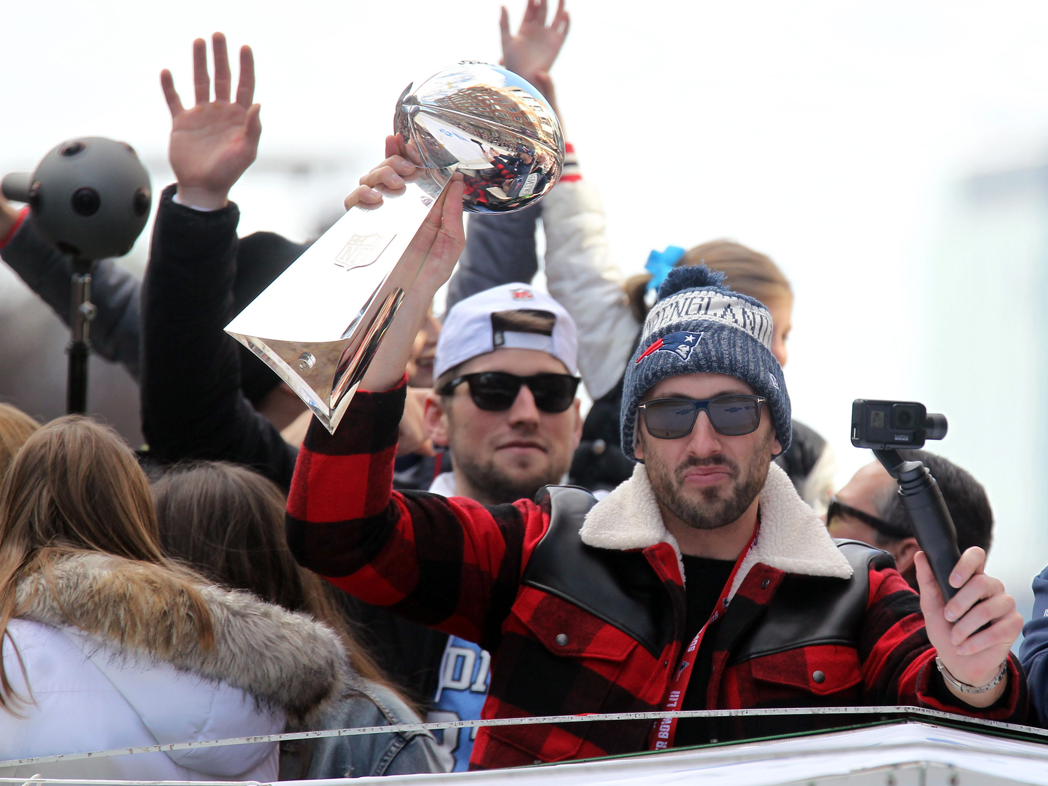 New England Patriots quarterback Brian Hoyer holds the Lombardi Trophy during the Super Bowl LIII championship parade.