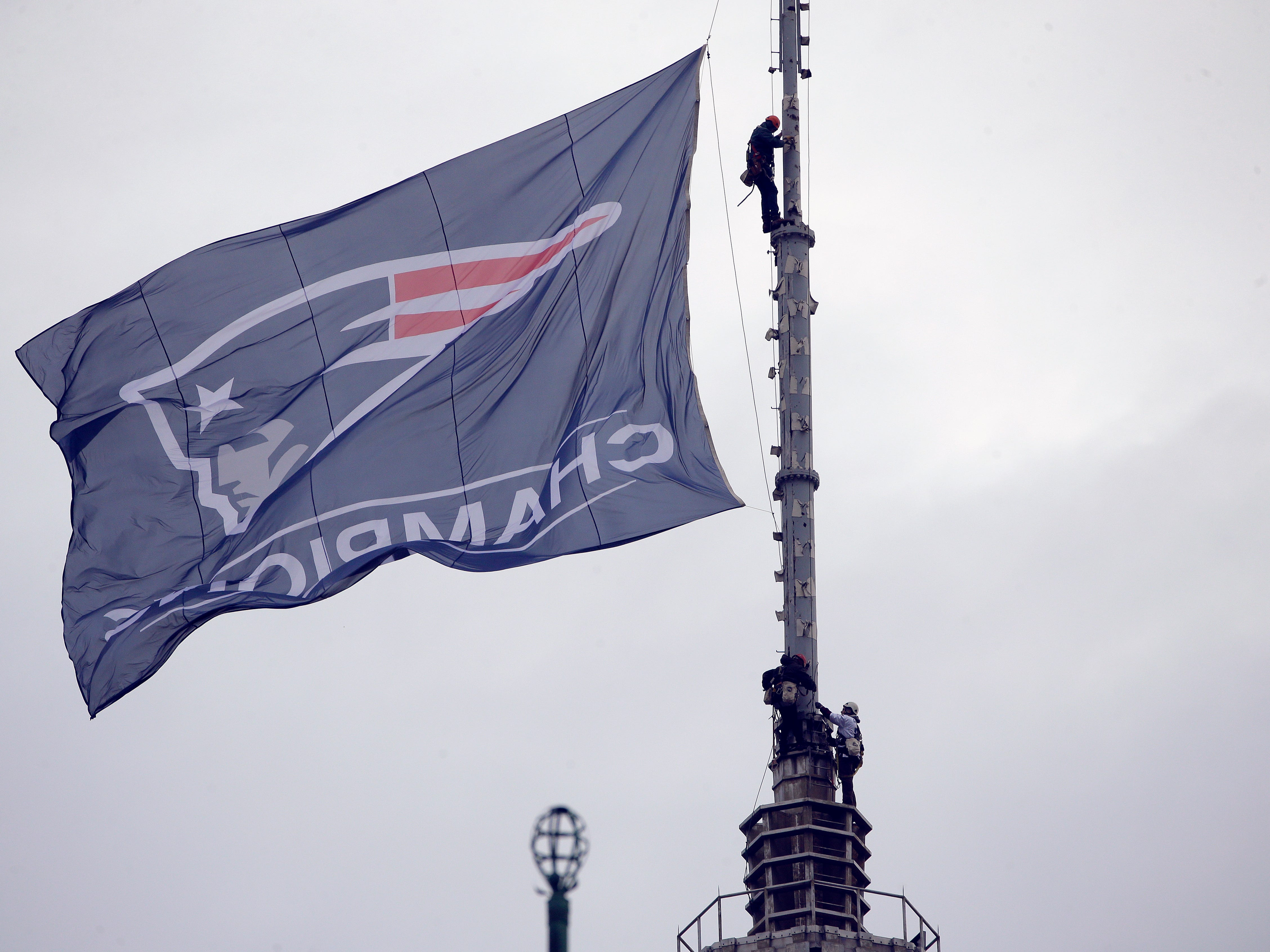 Workers secure a New England Patriots banner on a pole before the team parades through downtown Boston to celebrate their win over the Los Angeles Rams in Sunday's NFL Super Bowl 53 football game in Atlanta. (AP Photo/Steven Senne)
