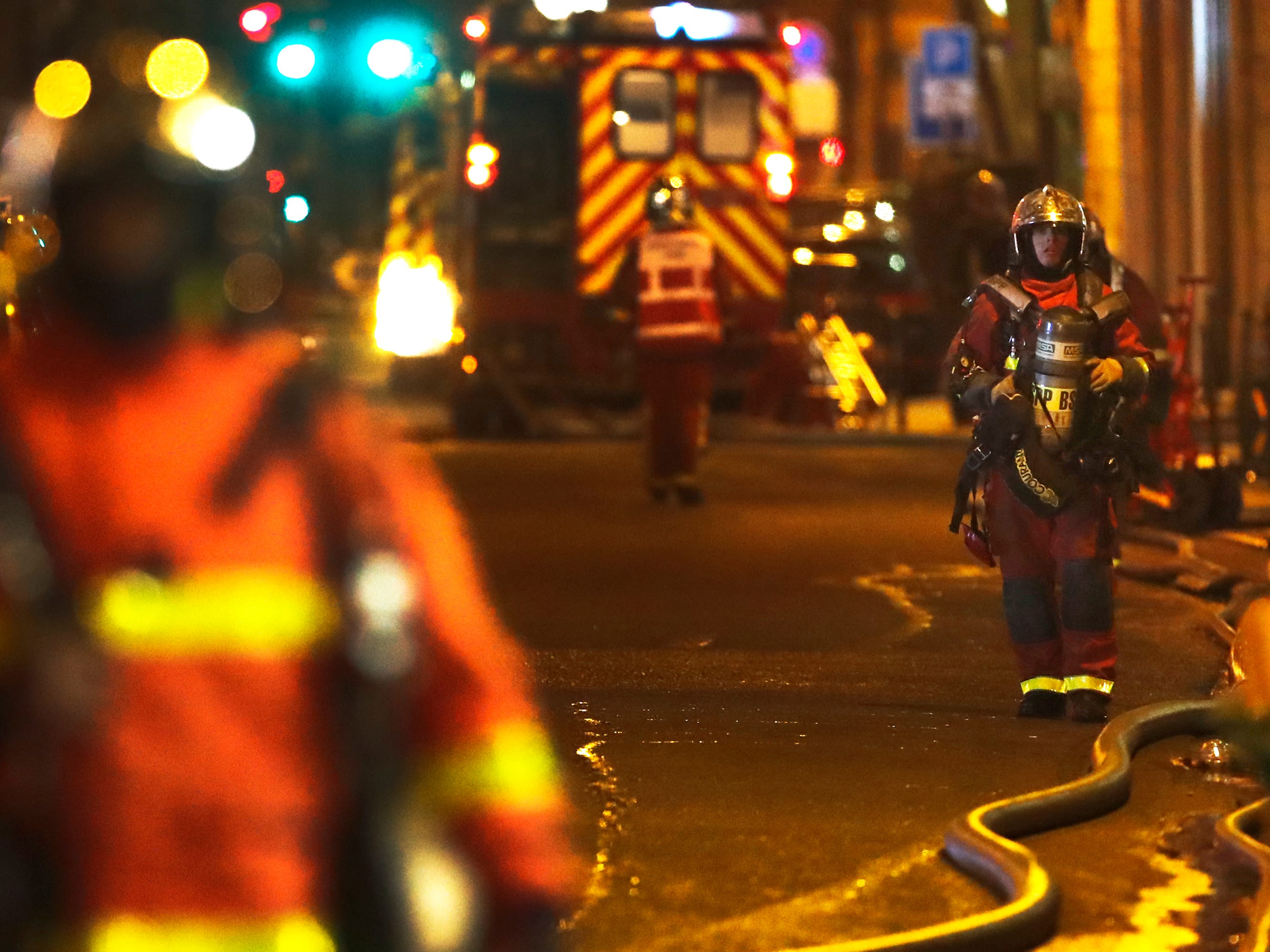 Firefighters stand on the scene of a fire in Paris,  Feb. 5, 2019.