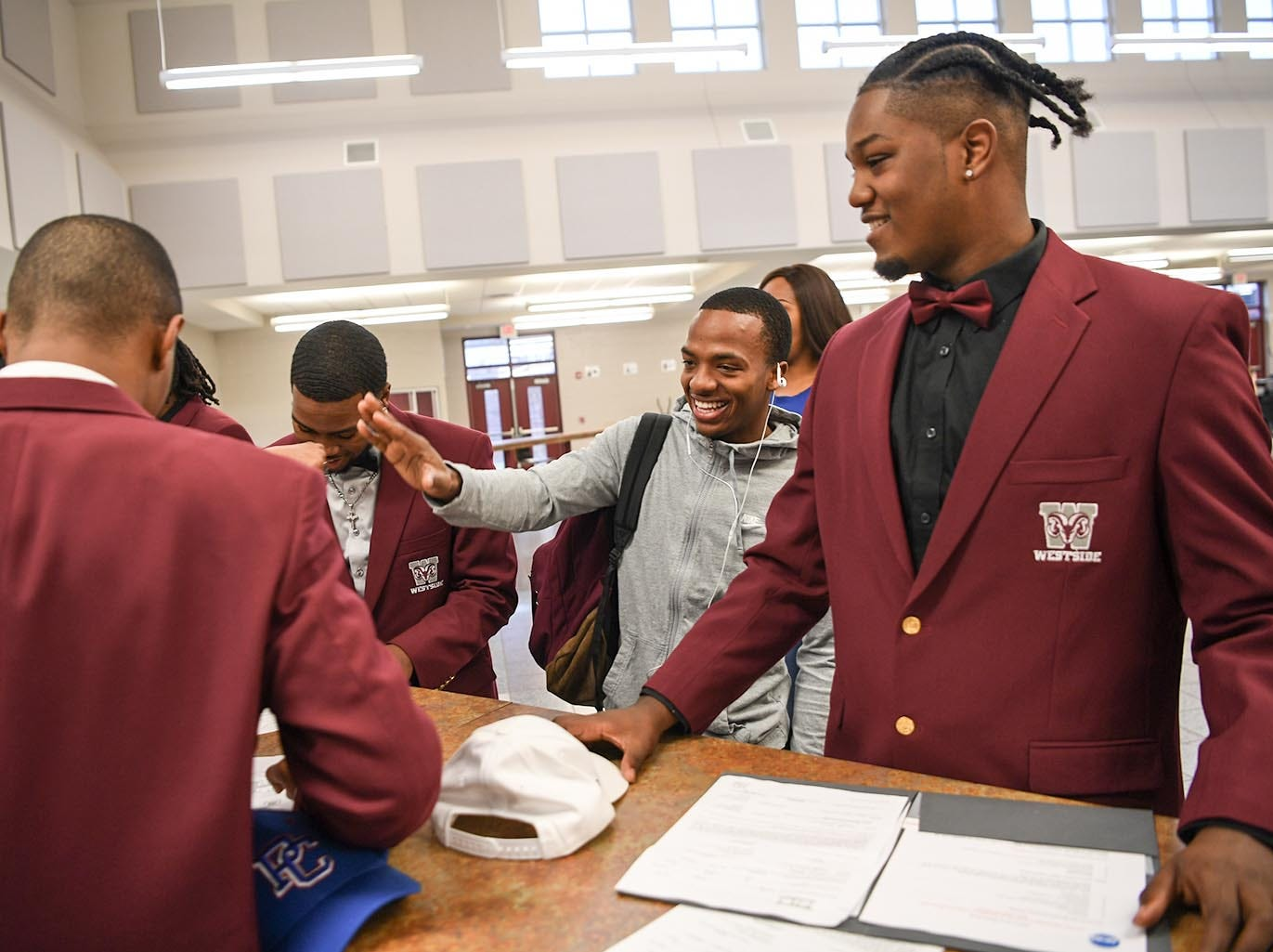 Traye Carson, middle, congratulates former football teammates, including Florida Intstitute of Technology signee Ty Ty Danzy, right, one of seven athletes from Westside High School football to sign a National Letter of Intent at Westside High School in Anderson Wednesday. Newberry College signees Zach Howard, Devante Gambrell, Wingate University signees Nasir Evans and K.D. Fant-Miles, Presbyterian College signees Paul Johnson and Tim Johnson, and Florida Intstitute of Technology signee Ty Ty Danzy.