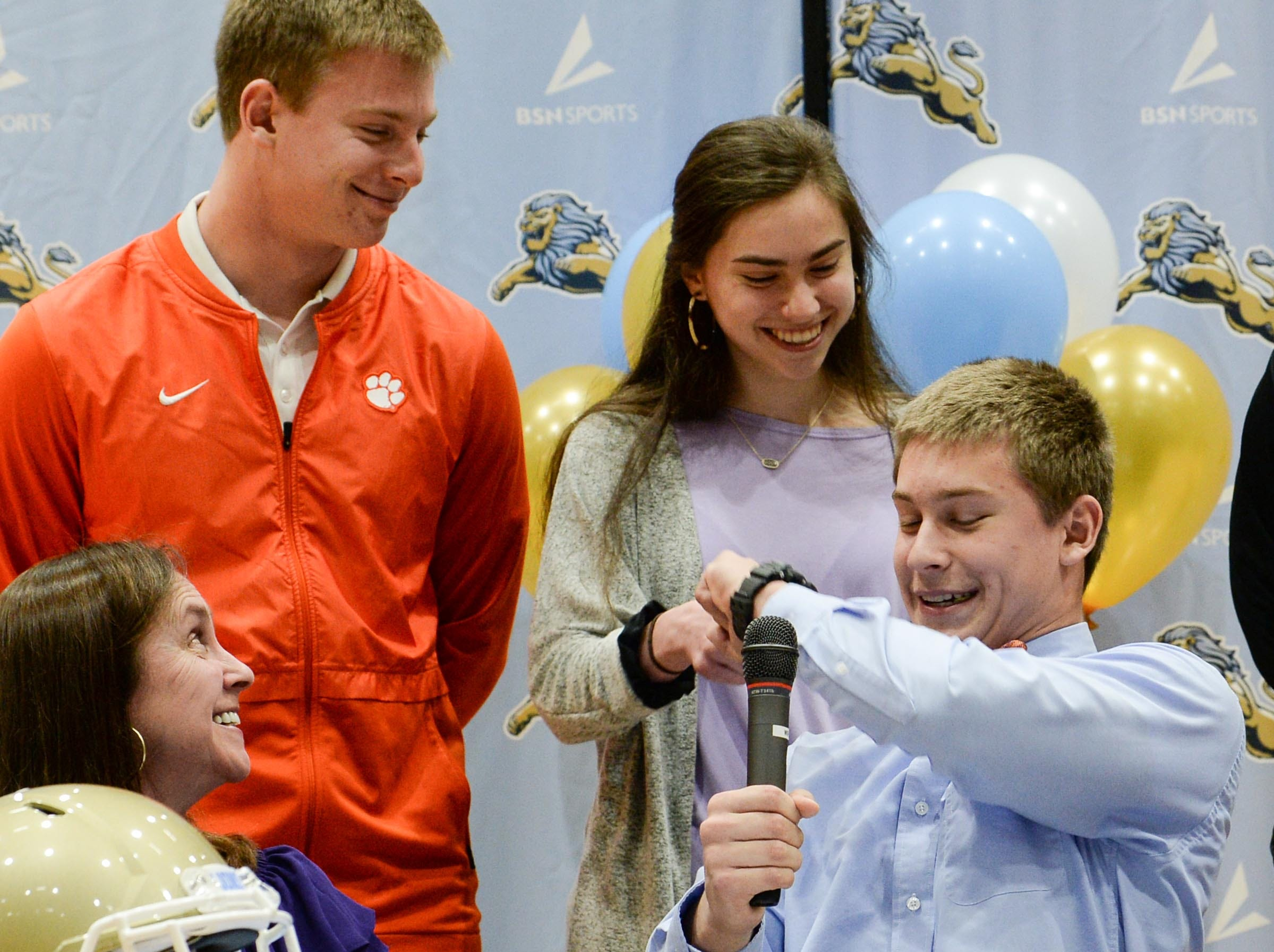Clemson University football preferred walk on signee Matthew Maloney gives a fist bump to his sister Jessica Maloney near his brother Jacob and mother Tina during National Letter of Intent signing day at D.W. Daniel High School in Central Wednesday.