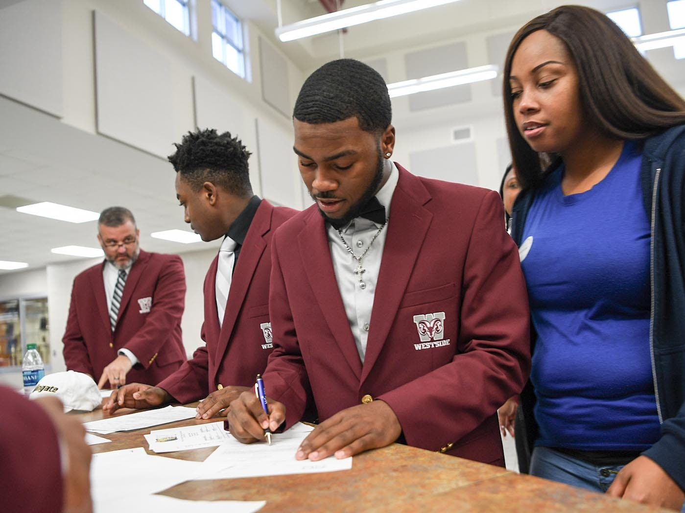 Wingate University signees K.D. Fant-Miles, left, fills out paperwork near his mother Laura Fant, right, as one of seven athletes from Westside High School football to sign a National Letter of Intent at Westside High School in Anderson Wednesday. Newberry College signees Zach Howard, Devante Gambrell, Wingate University signees Nasir Evans and K.D. Fant-Miles, Presbyterian College signees Paul Johnson and Tim Johnson, and Florida Intstitute of Technology signee Ty Ty Danzy.