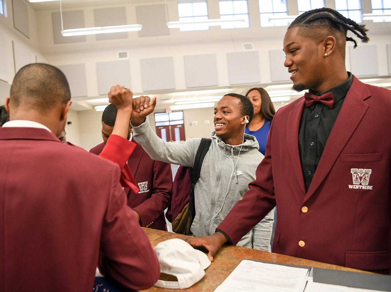 Traye Carson, middle, congratulates former football teammates, including Florida Intstitute of Technology signee Ty Ty Danzy, right, one of eight athletes from Westside High School football to sign a National Letter of Intent at Westside High School in Anderson Wednesday. Newberry College signees Zach Howard, Devante Gambrell, Wingate University signees Nasir Evans and K.D. Fant-Miles, Presbyterian College signees Paul Johnson and Tim Johnson, and Florida Intstitute of Technology signee Ty Ty Danzy.