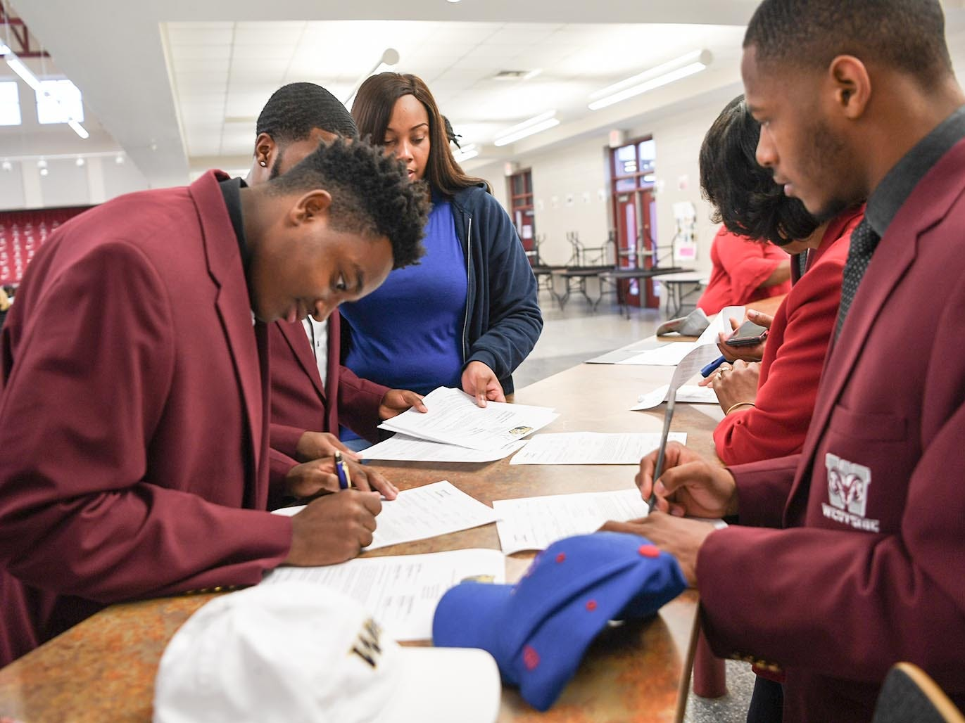 Wingate University signee Nasir Evans, left, fills out paperwork near Presbyterian College signee Paul Johnson, right, and five other teammates from Westside High School football on National Letter of Intent day at Westside High School in Anderson Wednesday. Newberry College signees Zach Howard, Devante Gambrell, Wingate University signees Nasir Evans and K.D. Fant-Miles, Presbyterian College signees Paul Johnson and Tim Johnson, and Florida Intstitute of Technology signee Ty Ty Danzy.