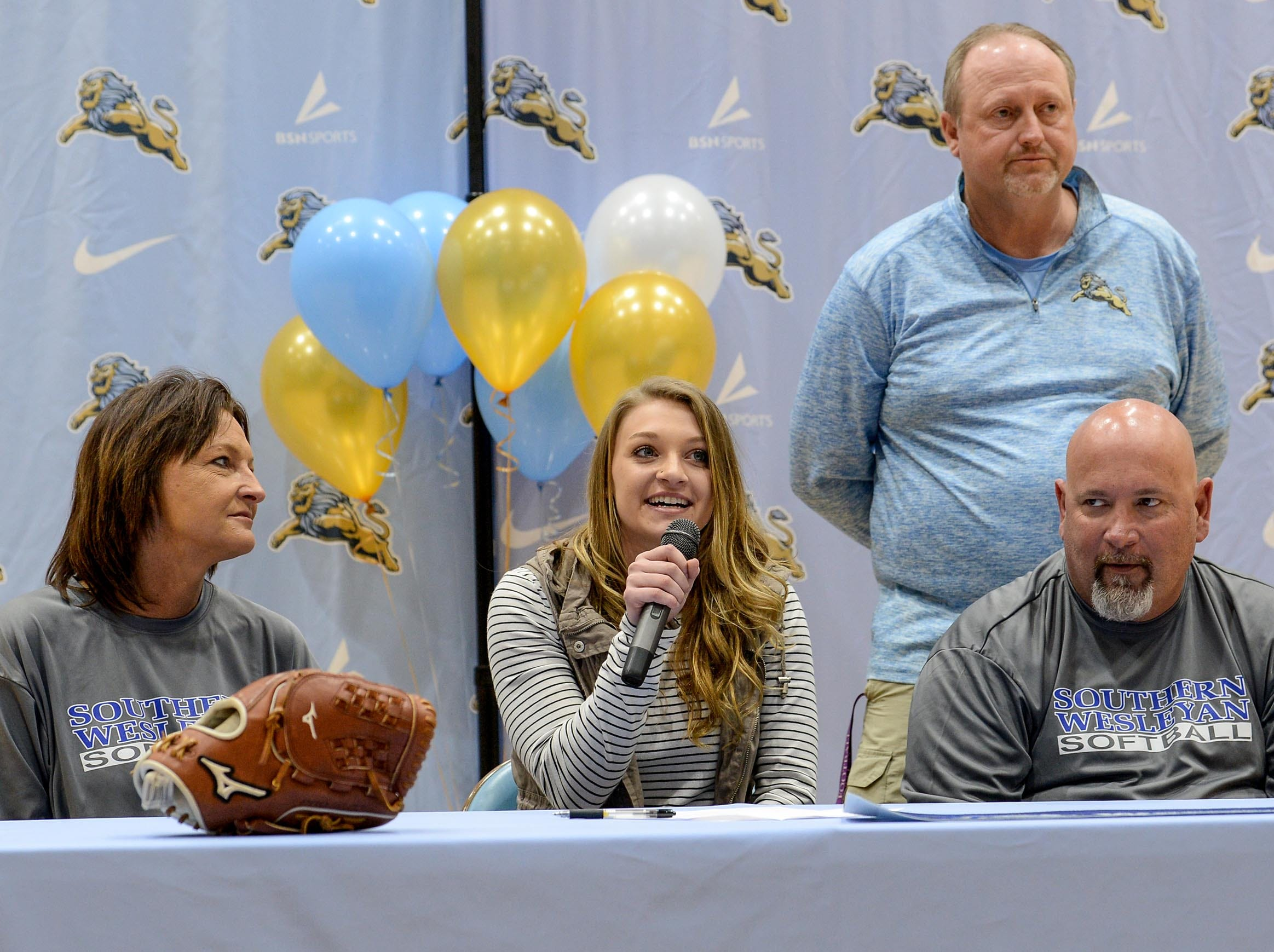 Southern Wesleyan University softball signee Makayla Sexton speaks near parents Kevin and Lydia Sexton and coach Andy Swords during National Letter of Intent signing day at D.W. Daniel High School in Central Wednesday.