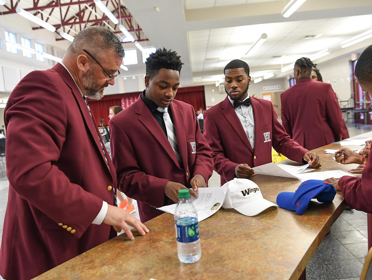 Westside football coach Scott Earley, left, watches Wingate University signee Nasir Evans, fill out paperwork near Wingate University signee K.D. Fant-Miles, right, and five other teammates from Westside High School football on National Letter of Intent day at Westside High School in Anderson Wednesday.