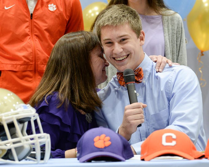 Clemson University football preferred walk on signee Matthew Maloney gets a hug from his mother Tina during National Letter of Intent signing day at D.W. Daniel High School in Central Wednesday.
