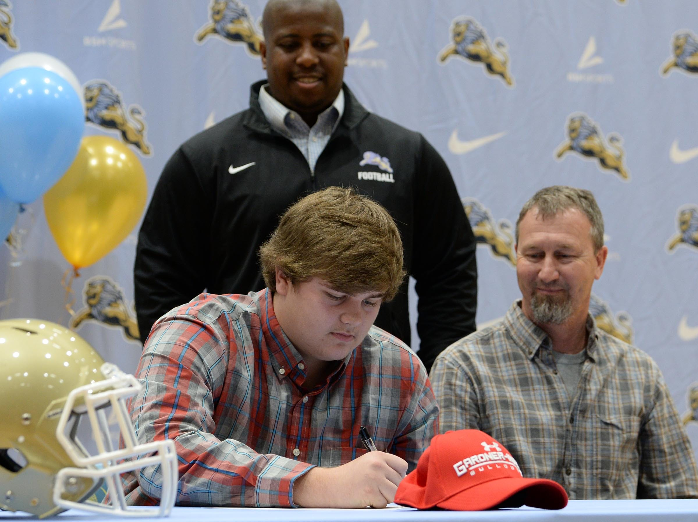 Gardner Webb football preferred walk on signee Cambel Guffee signs near father Gary Guffee and D.W. Daniel coach Jeff Fruster during National Letter of Intent signing day in Central Wednesday.
