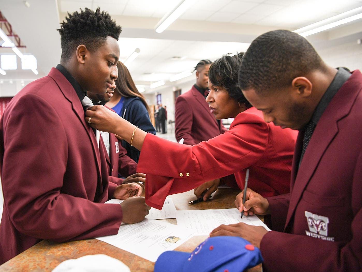Wingate University signee Nasir Evans, left, gets his tie checked by his mother Valerie Evans, right, while filling out paperwork near Presbyterian College signee Tim Johnson, right, and five other teammates from Westside High School football on National Letter of Intent day at Westside High School in Anderson Wednesday.