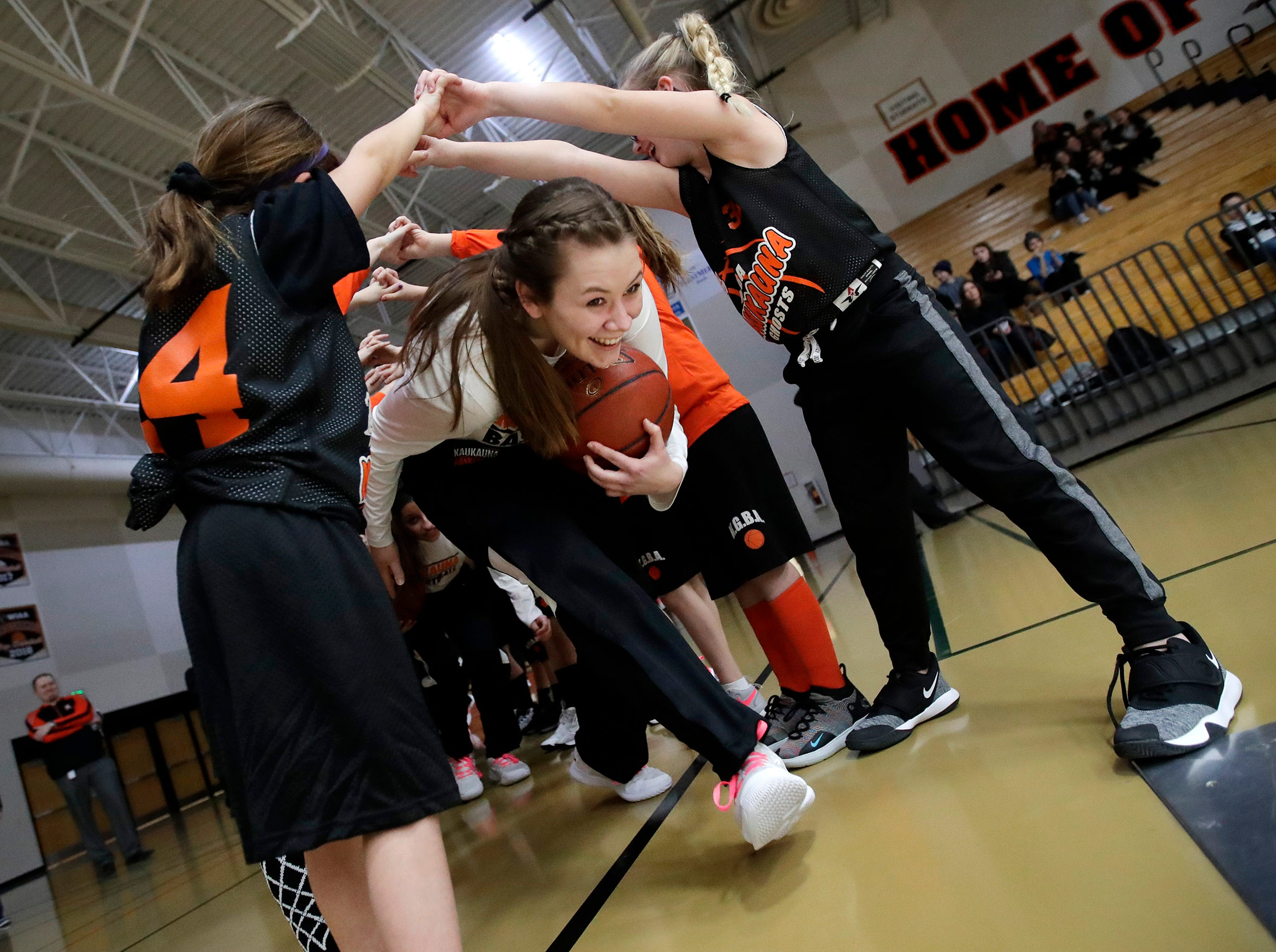 Kaukauna High School's Gabby Djupstrom, a senior on the team, runs through the arms of the third-grade Kaukauna basketball team as she takes the court Tuesday, Feb. 5, 2019, in Kaukauna, Wis.