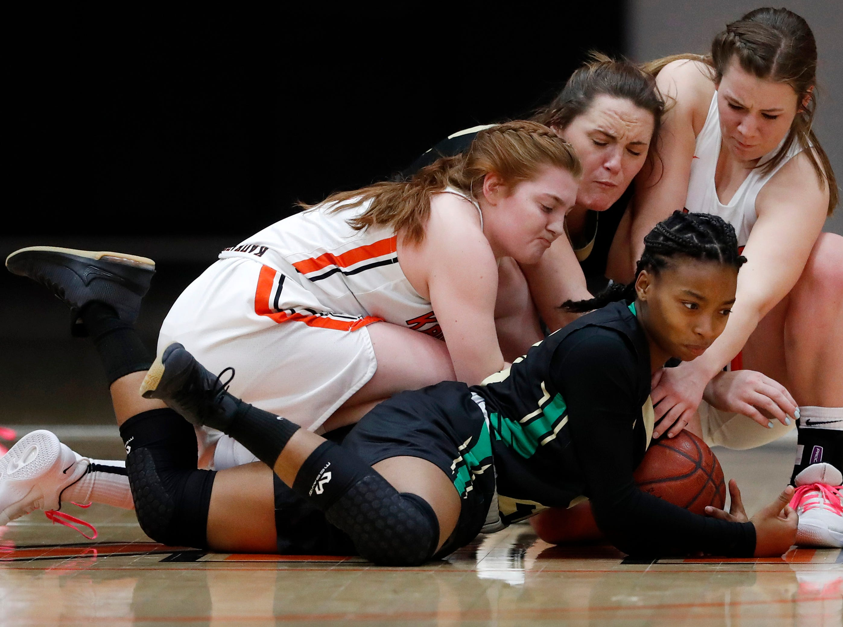 Oshkosh North High School's Nydia Griffin secures the ball on the ground to before passing it to a teammate to keep it from Kaukauna High School's Lindsey Laflen (left) and GAbby Djupstrom (right) Tuesday, Feb. 5, 2019, in Kaukauna, Wis. Danny Damiani/USA TODAY NETWORK-Wisconsin
