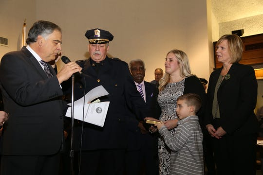 With family at his side, New Aberdeen Police Chief Rick Derechailo (center) is  sworn in by Mayor Fred Tagliarini (left) last month.