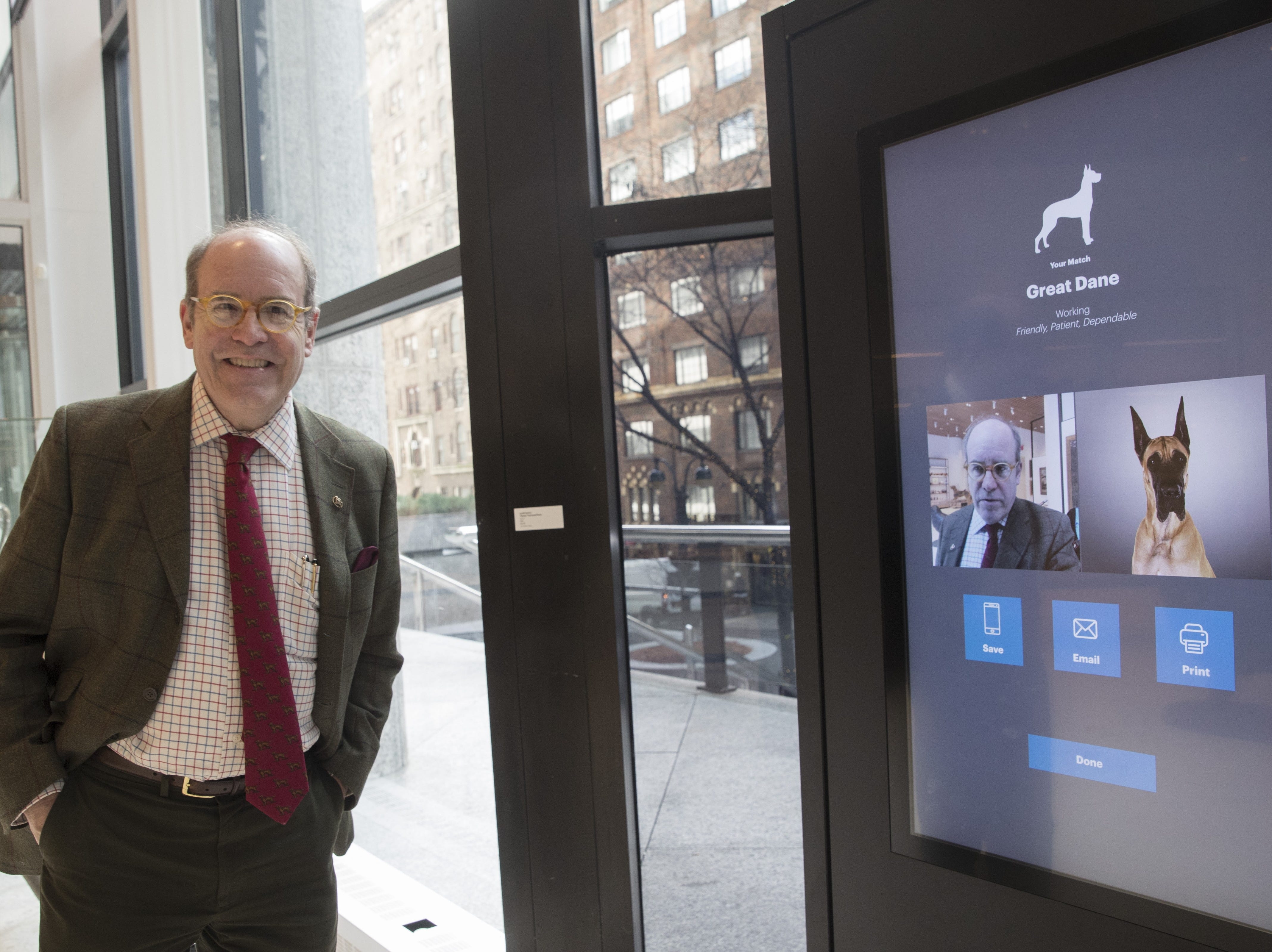 Alan Fausel, Executive Director of The American Kennel Club Museum of the Dog, smiles after finding his dog breed match at the Find Your Match interactive kiosk during a tour of the museum in New York. This Wednesday, Jan. 9, 2019, photo shows American Kennel Club Museum of the Dog's Executive Director Alan Fausel smiling after finding his dog breed match at the Find Your Match interactive kiosk during a tour of the museum in New York. The museum opens Feb. 8. (AP Photo/Mary Altaffer)
