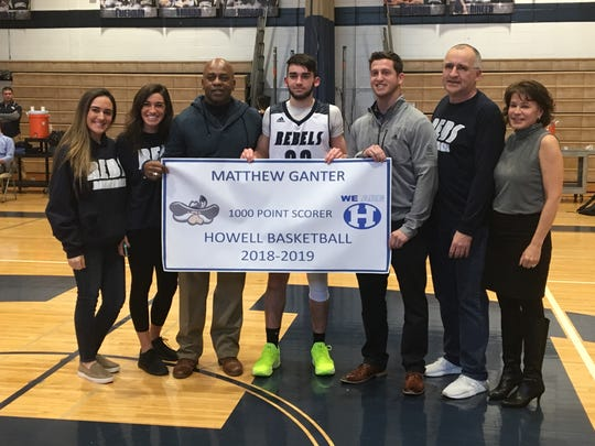 Howell's Matt Ganter (center) is joined by Bill Hill (third from the left), who was Howell's first 1,000th point scorer in boys basketball. Ganter's family surrounds them on Feb. 5, 2019. .